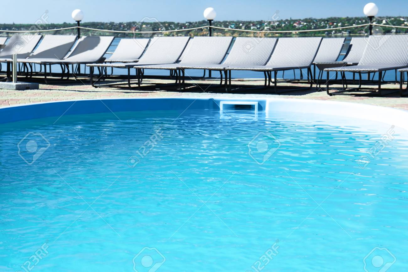 Outdoor Natural Gas Fire Pit Table, Swimming Pool With Clean Blue Water And Lounge Chairs Outdoors Stock Photo Picture And Royalty Free Image Image 108961174