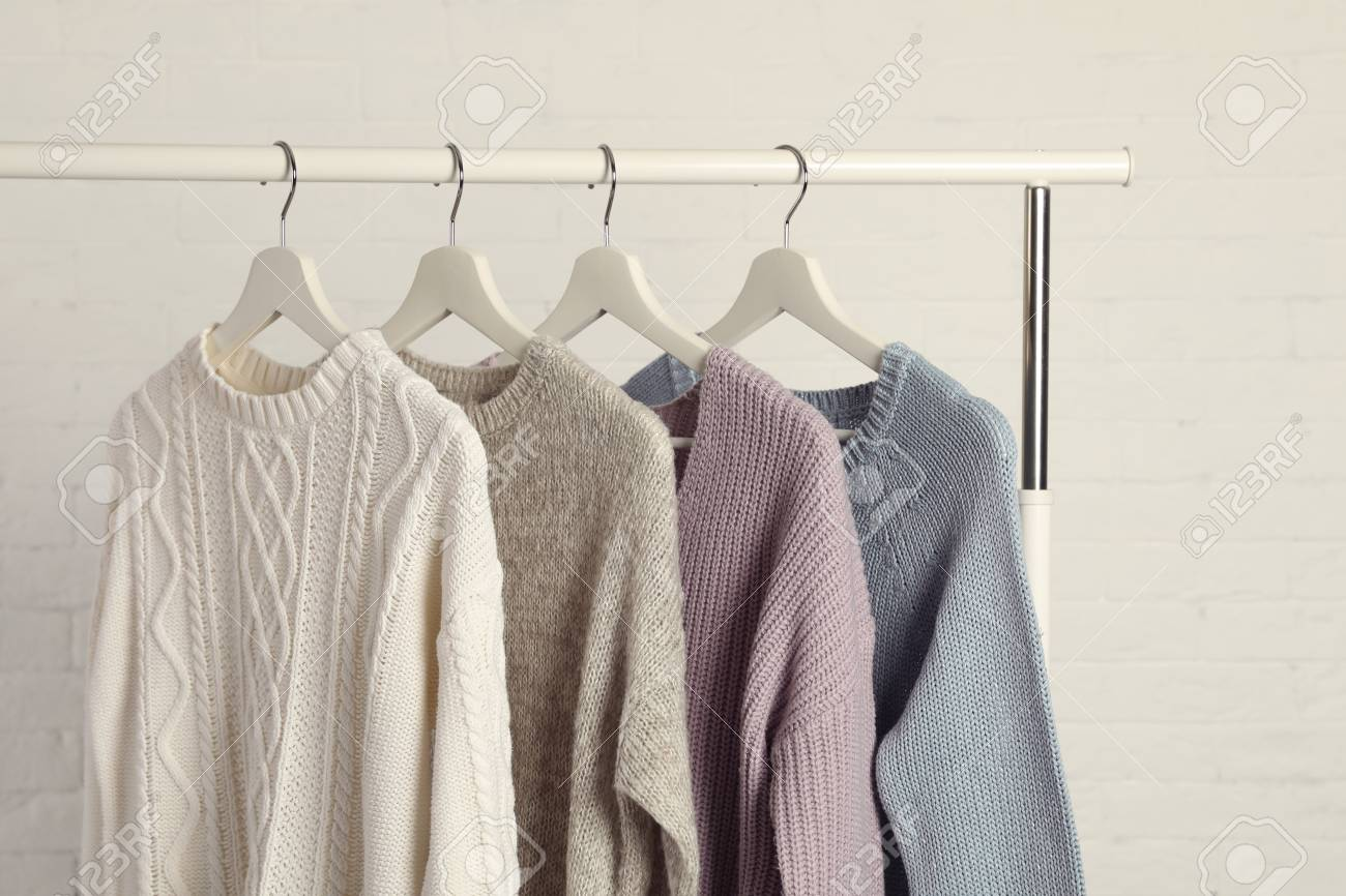 Collection of warm sweaters hanging on rack against white brick..