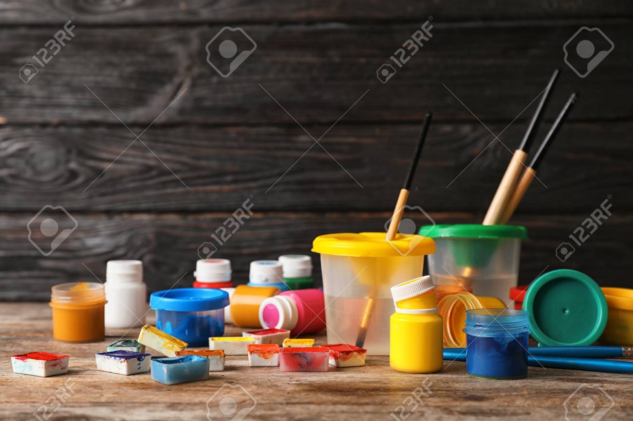 Set Of Child Painting Materials On Table Near Wooden Wall Space