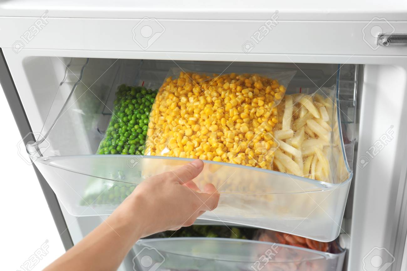 Woman opening refrigerator drawer with frozen vegetables, closeup - 112074980