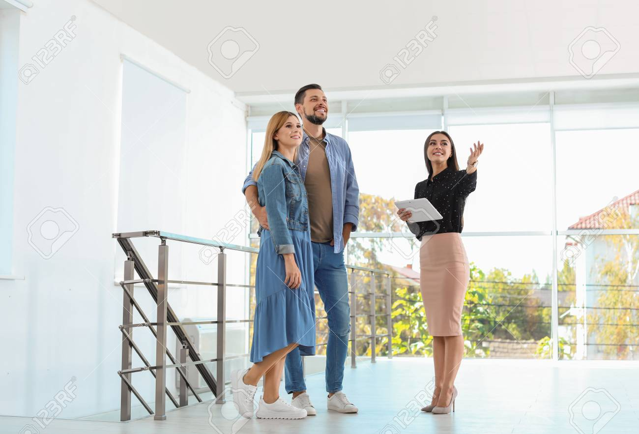 Female real estate agent showing new house to couple, indoors - 112536623