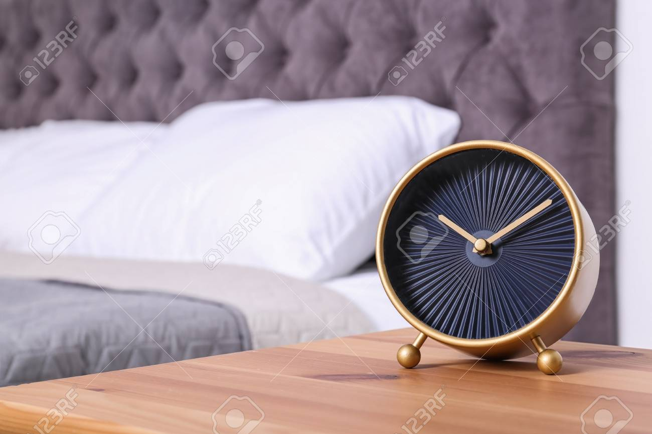 Stylish alarm clock on nightstand in bedroom. Space for text