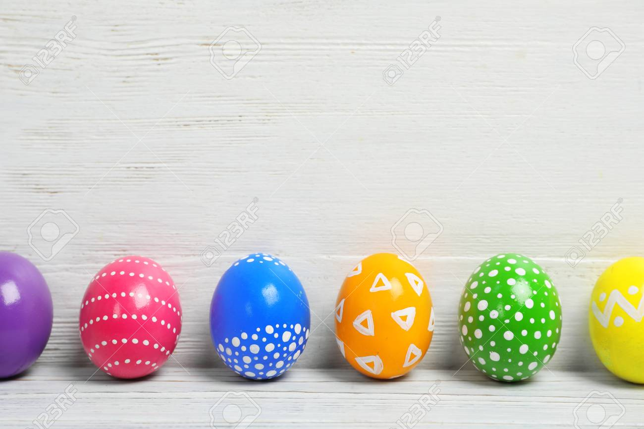 Decorated Easter Eggs On Table Near Wooden Wall Space For Text