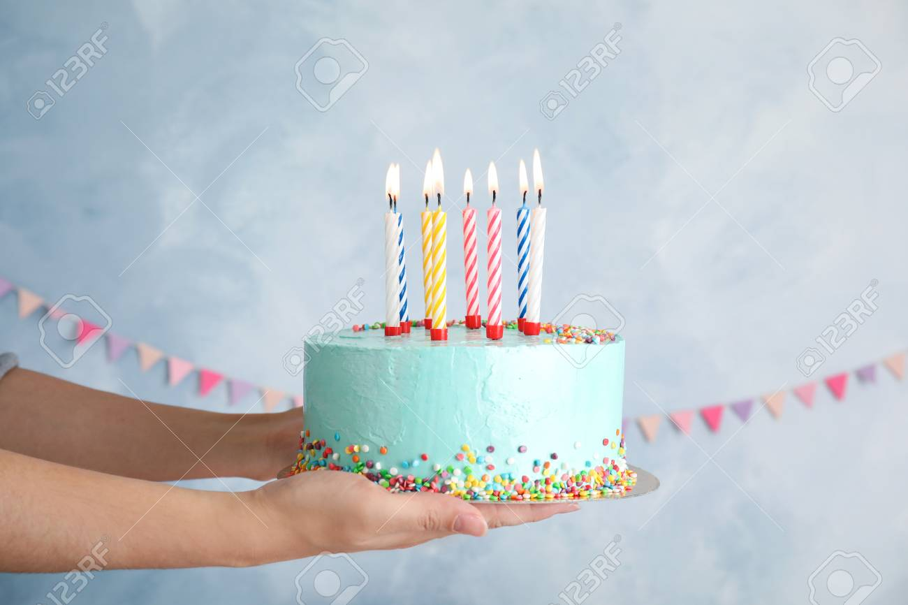 Woman Holding Fresh Delicious Birthday Cake With Candles On Color