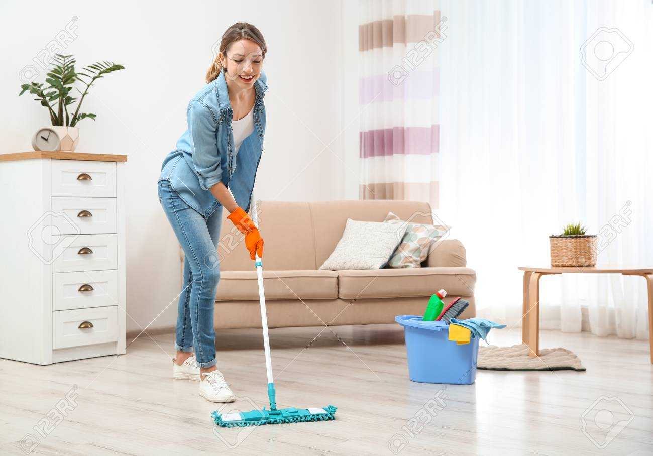 Young woman washing floor with mop in living room. Cleaning service - 114816414