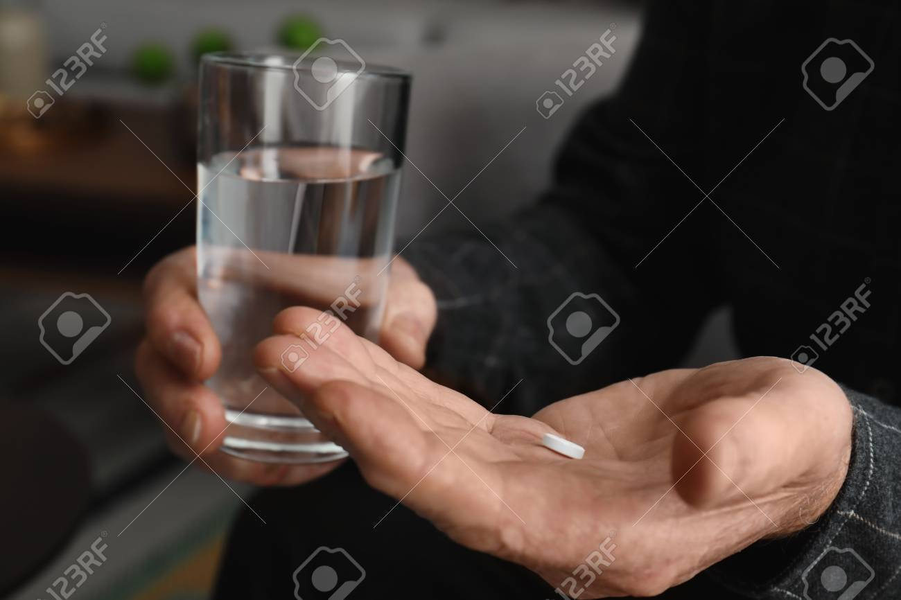 Senior man holding pill and glass of water indoors, closeup - 114652261