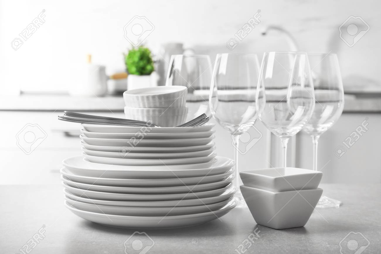 Set of clean dishes and cutlery on table in kitchen