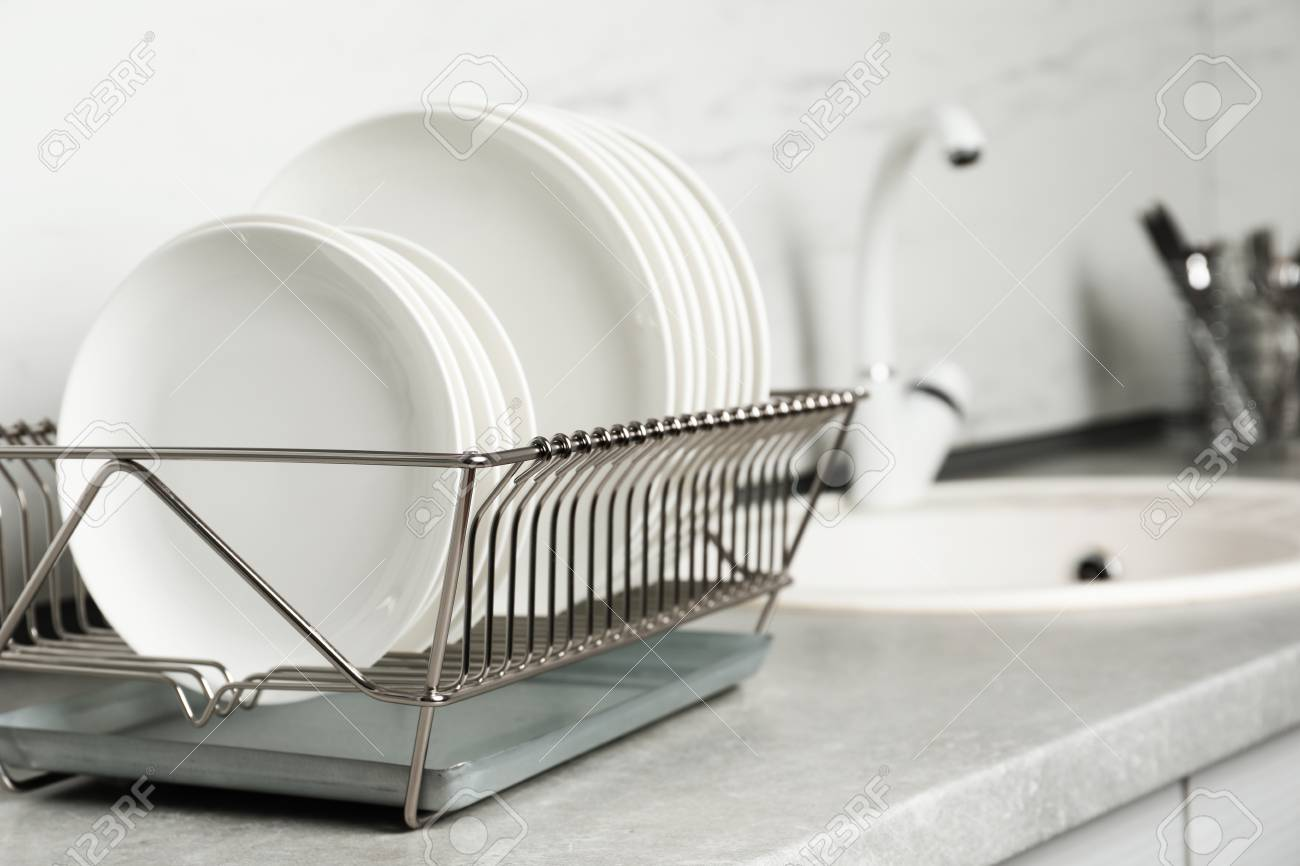 Drying rack with clean dishes on kitchen counter. Space for text - 115540261
