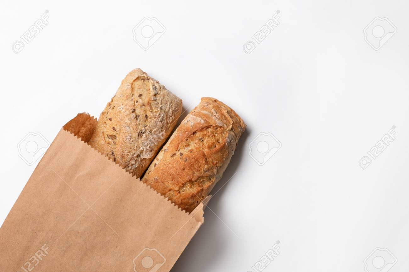 Paper bag with bread loaves on white background, top view. Space for text - 115724913