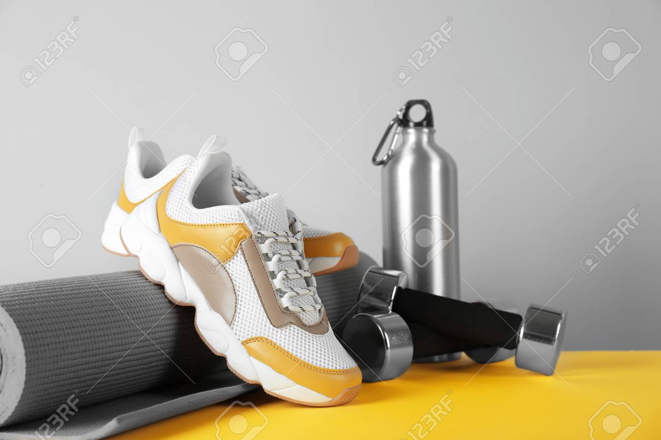 Composition of modern training shoes with mat, bottle and dumbbells on table - 115794047