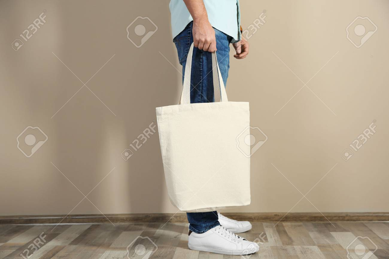Young man holding textile bag against color wall, closeup. Mockup for design - 116092678