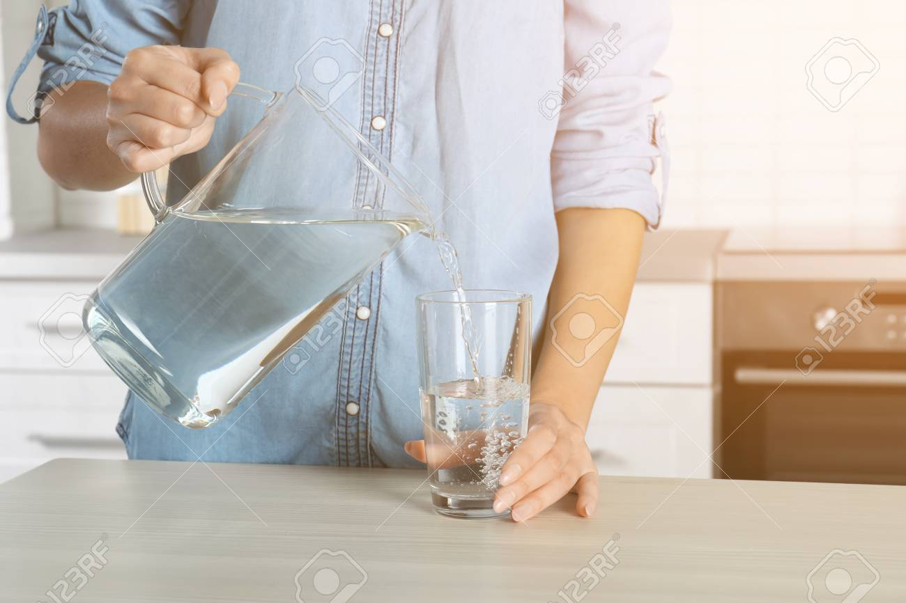 Woman pouring water into glass in kitchen, closeup. Refreshing drink - 117117981