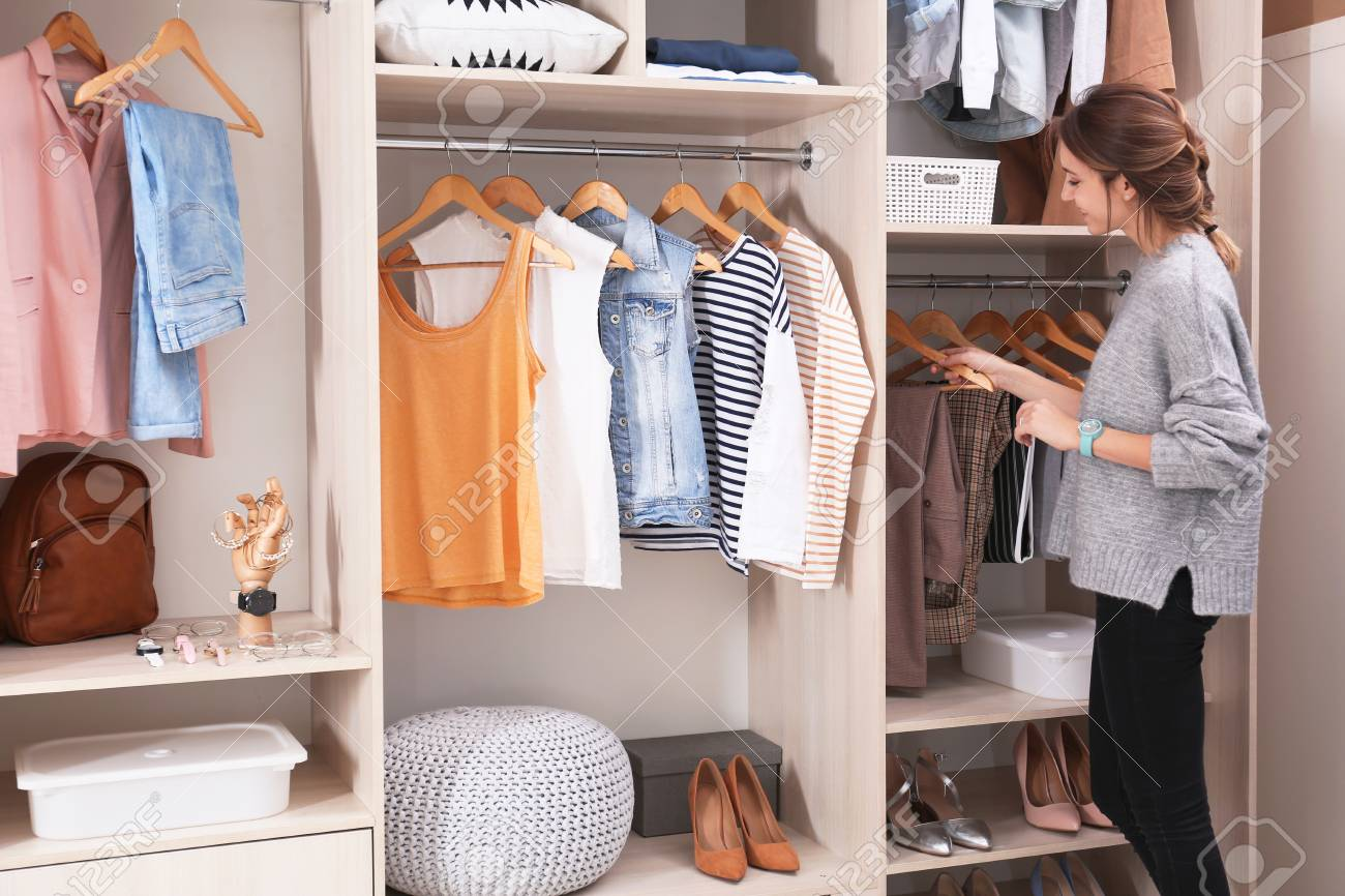 Woman choosing outfit from large wardrobe closet with stylish clothes, shoes and home stuff - 117993913