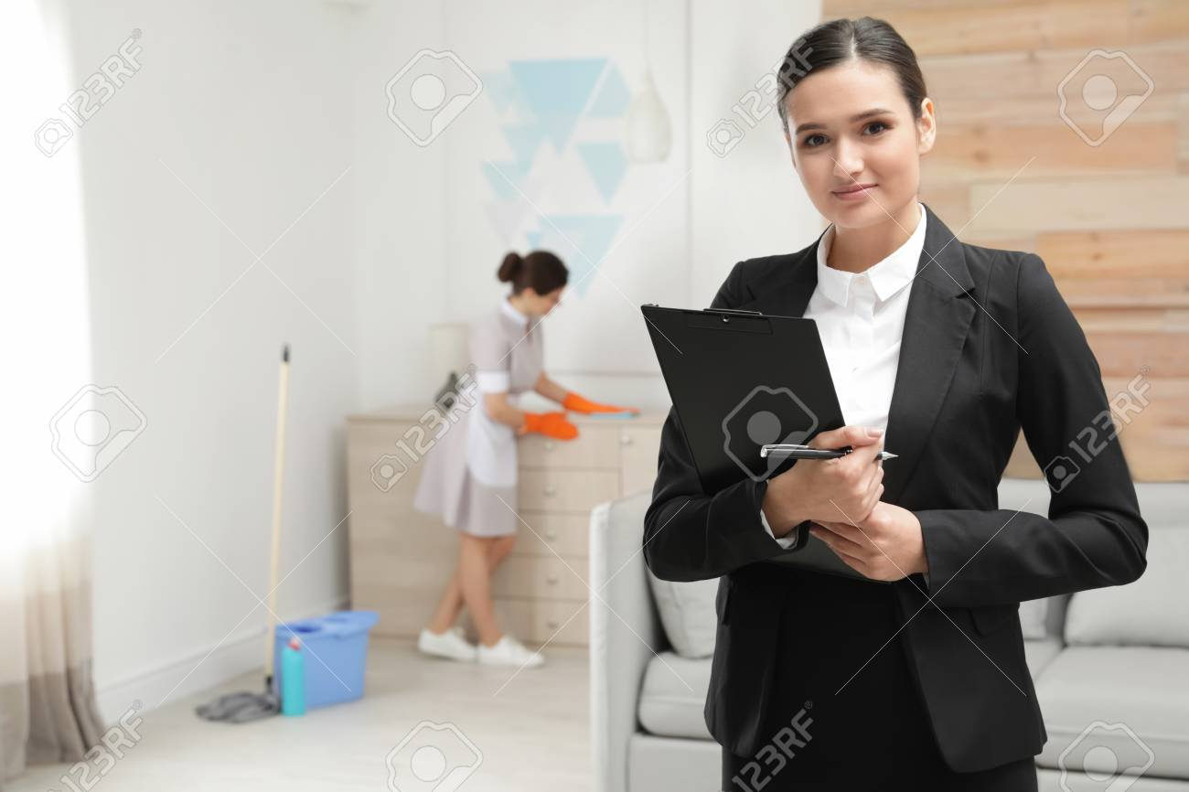 Housekeeping manager checking maid work in hotel room - 118399354