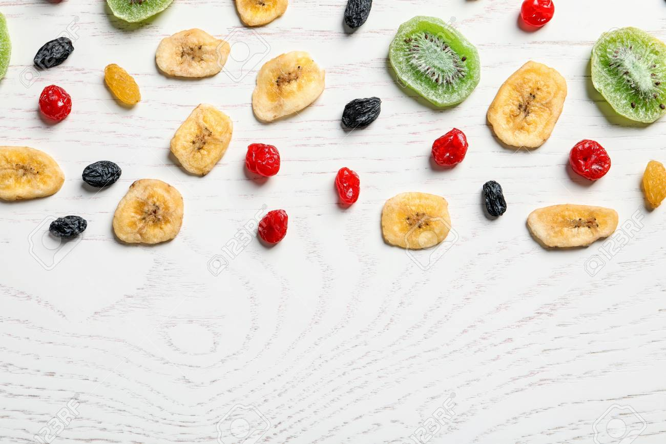 Flat lay composition with different dried fruits on wooden background,