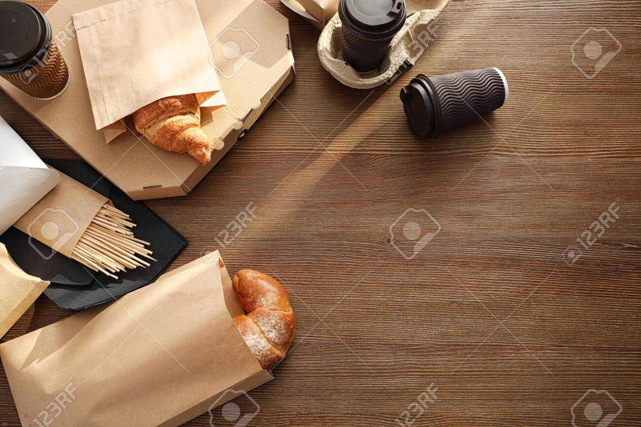 Paper bags with pastry and takeaway food on wooden table, top view. Space for text - 119159037