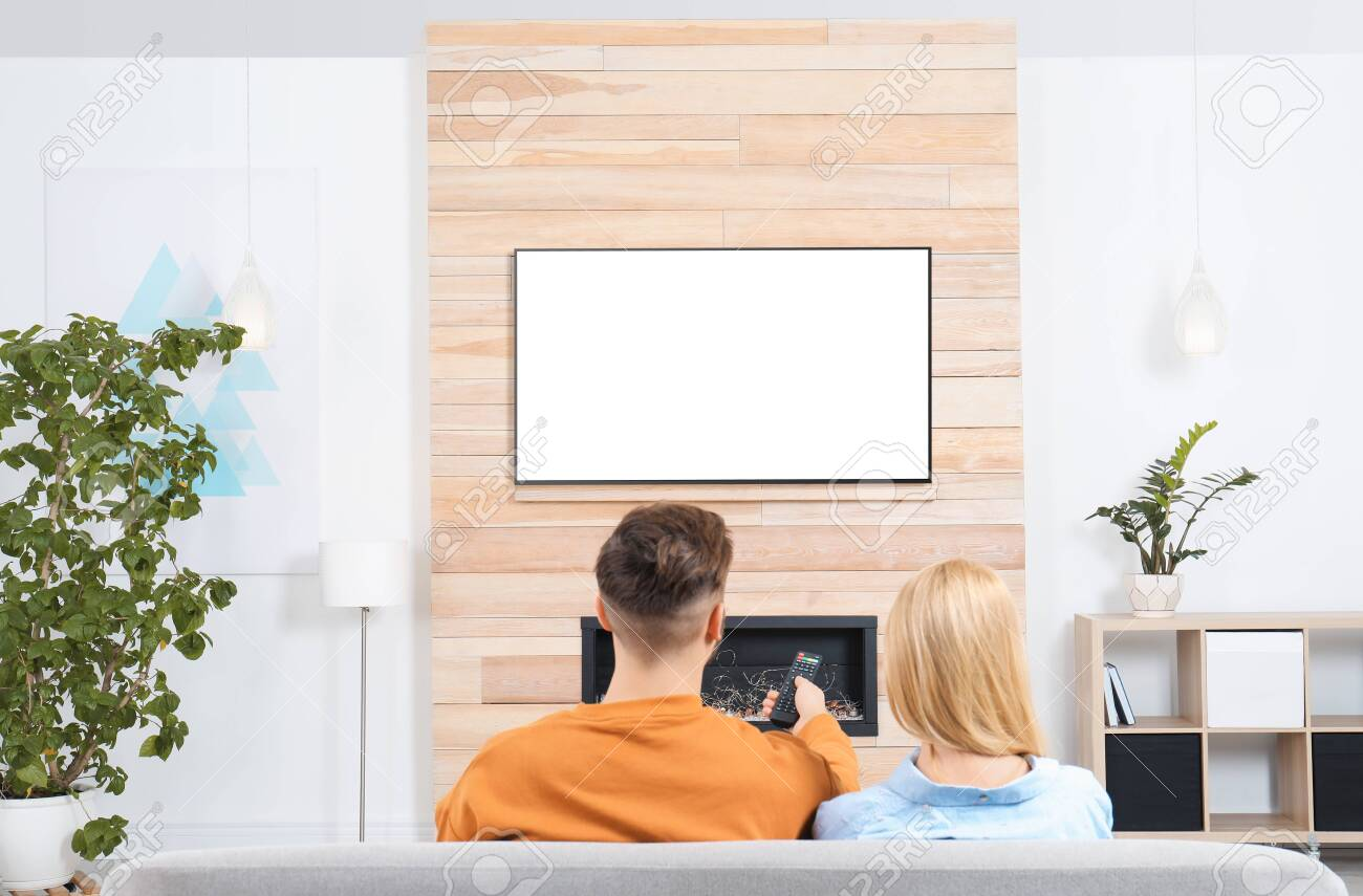 Couple watching TV on sofa in living room with decorative fireplace - 119138457