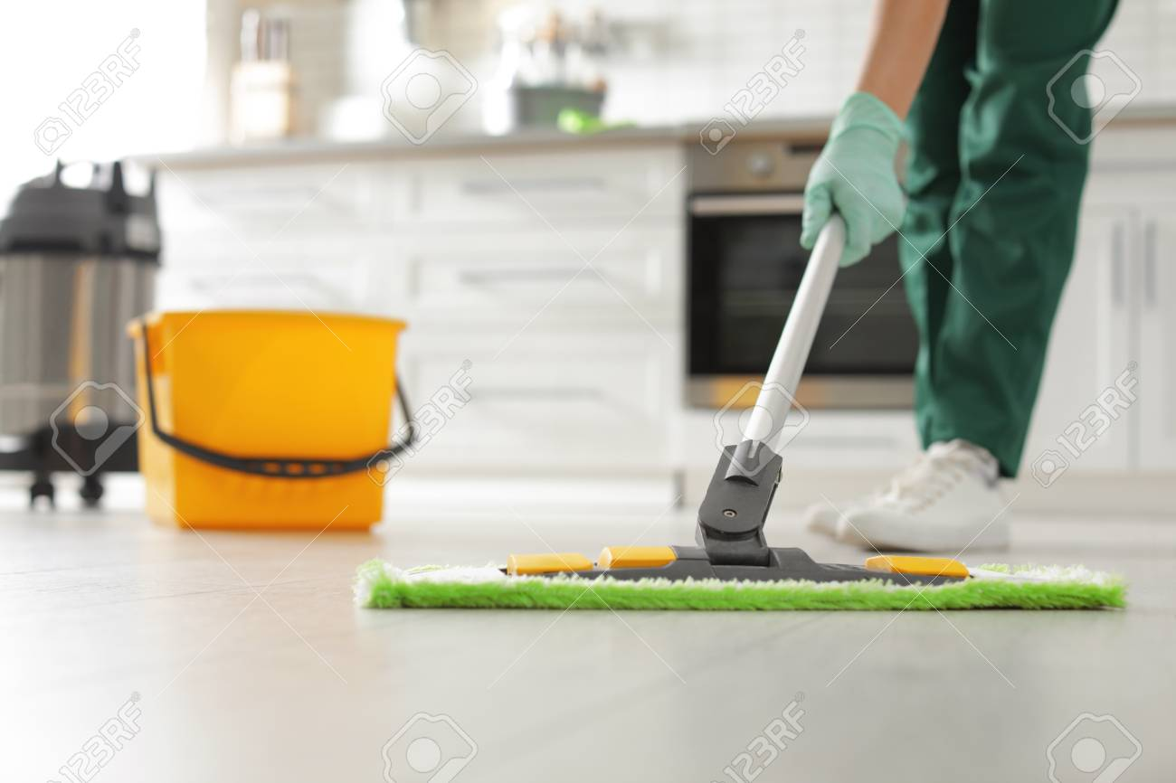 Professional janitor cleaning floor with mop in kitchen, closeup