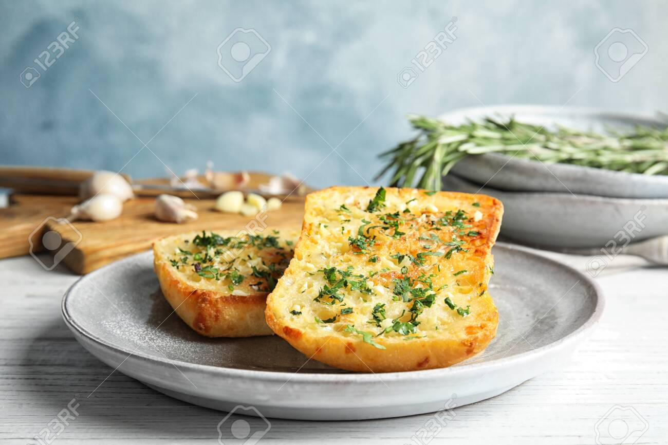 Plate with delicious homemade garlic bread on table - 120144082