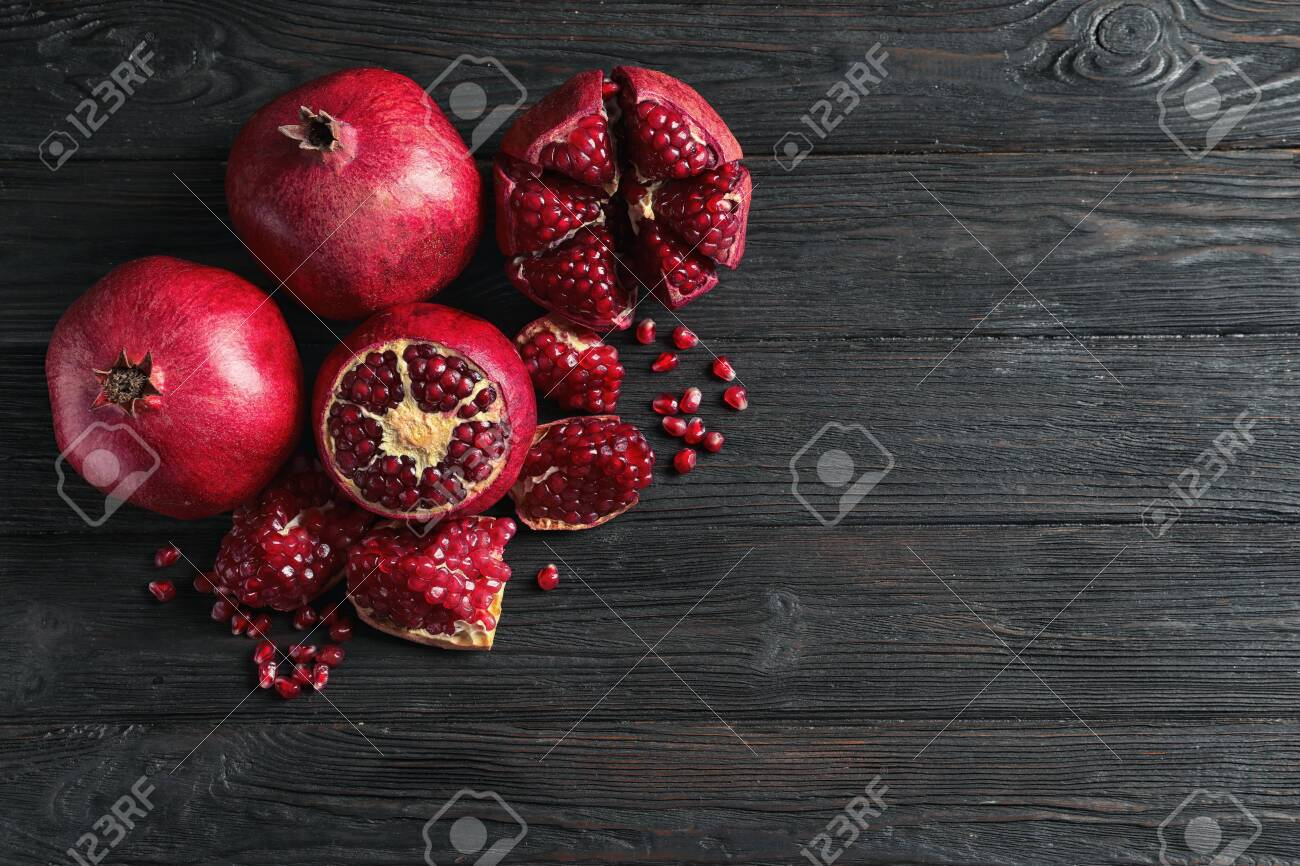 Ripe pomegranates and seeds on wooden background, flat lay with space for text - 120567766