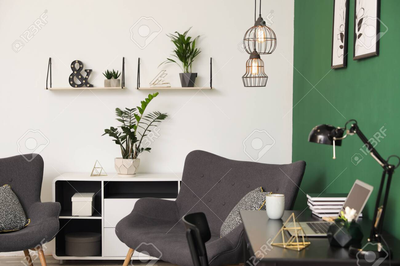 Modern living room interior with workplace near green wall - 120650756