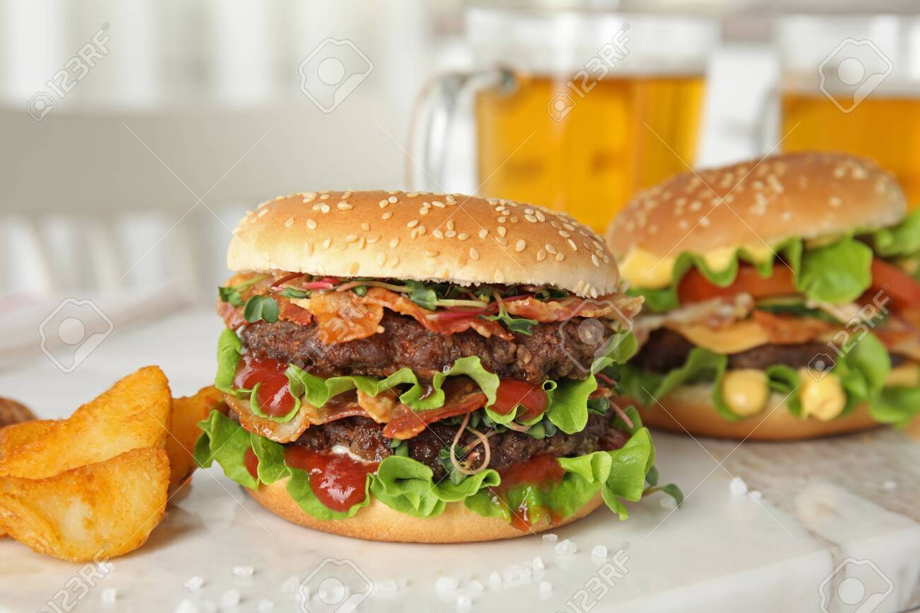 Tasty burgers with bacon and fried potatoes served on board - 120732084