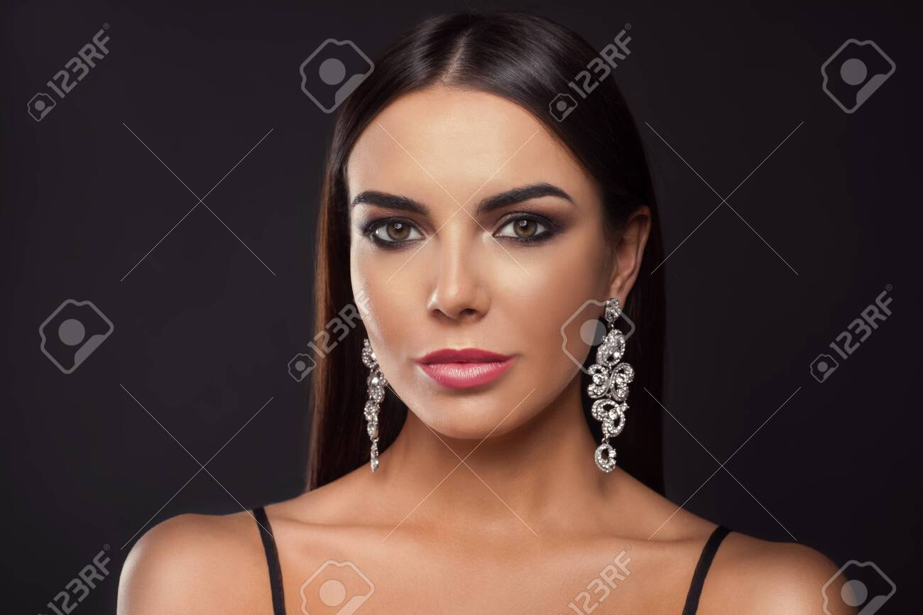 Beautiful young woman with elegant jewelry on dark background - 121107098