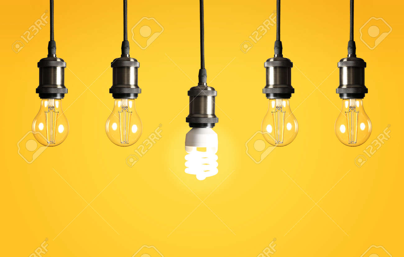 Many hanging lamp bulbs on color background. Symbol of idea and solution - 121431660