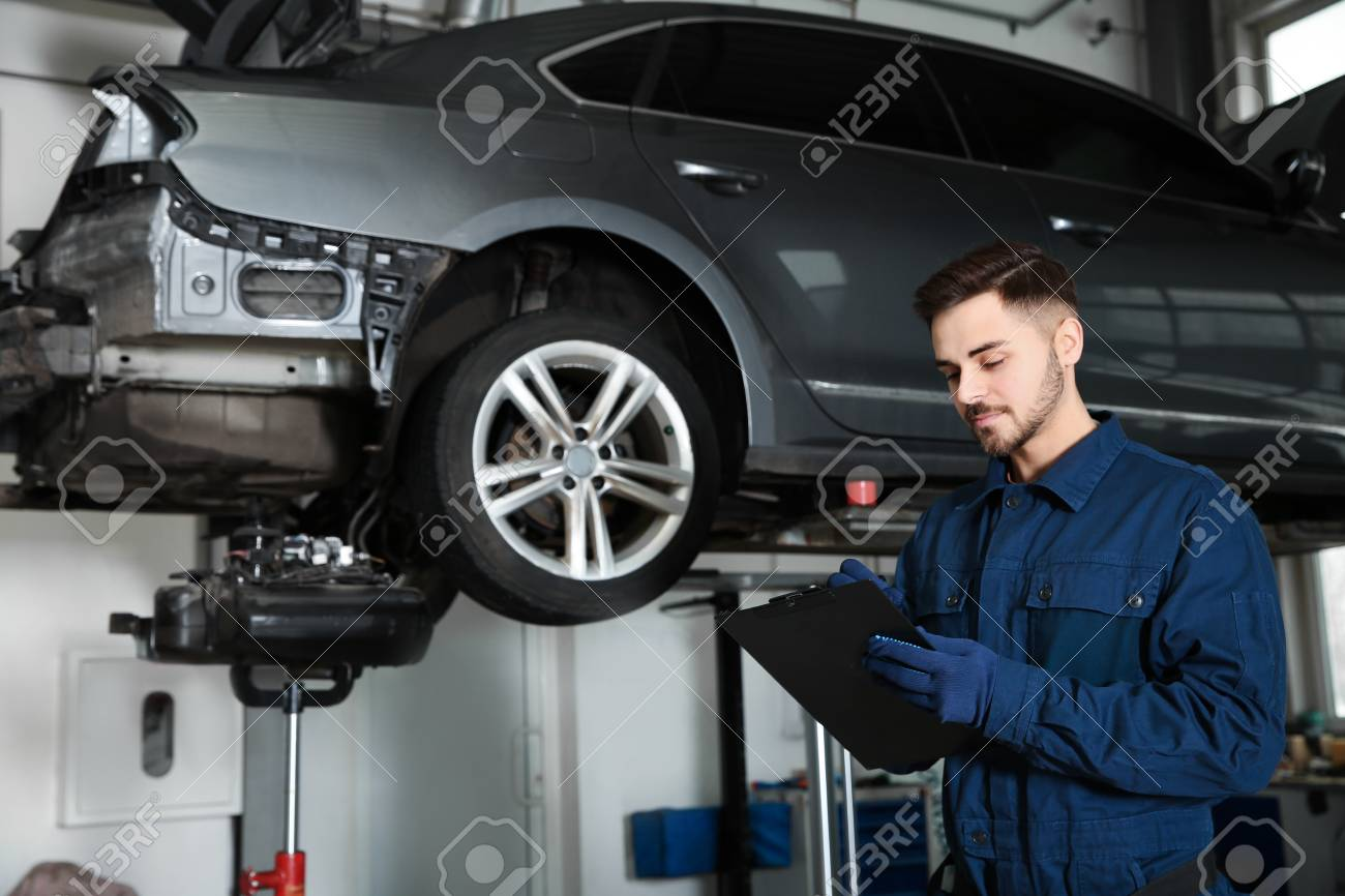 Technician checking car on hydraulic lift at automobile repair shop - 121780906