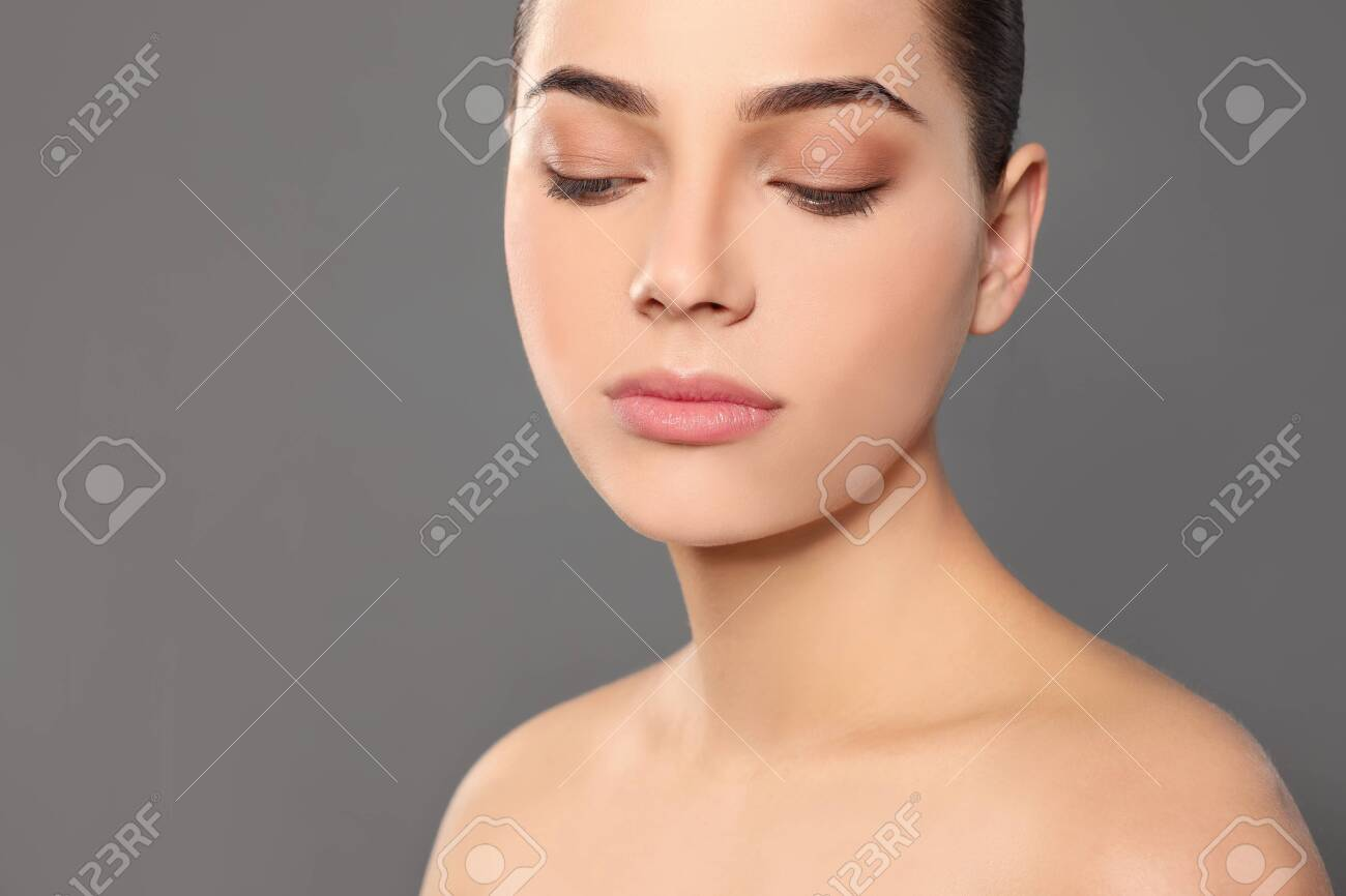 Portrait of young woman with beautiful face and natural makeup on color background, closeup - 123629221