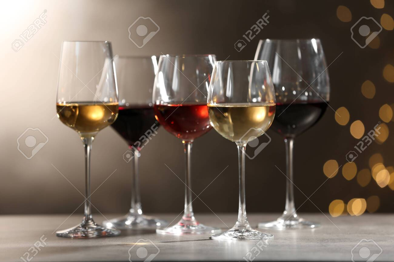 Glasses with different wines on grey table against defocused lights - 122529398