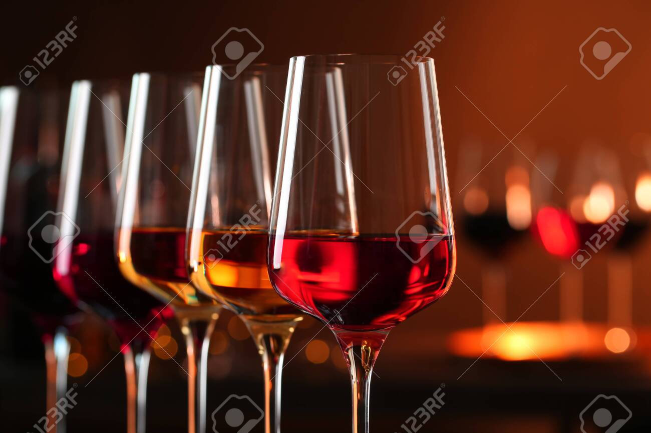 Row of glasses with different wines against blurred background, closeup. Space for text - 122530365