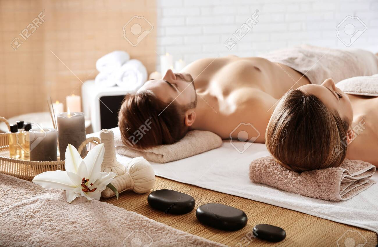 Young couple with spa essentials in wellness center - 123201704