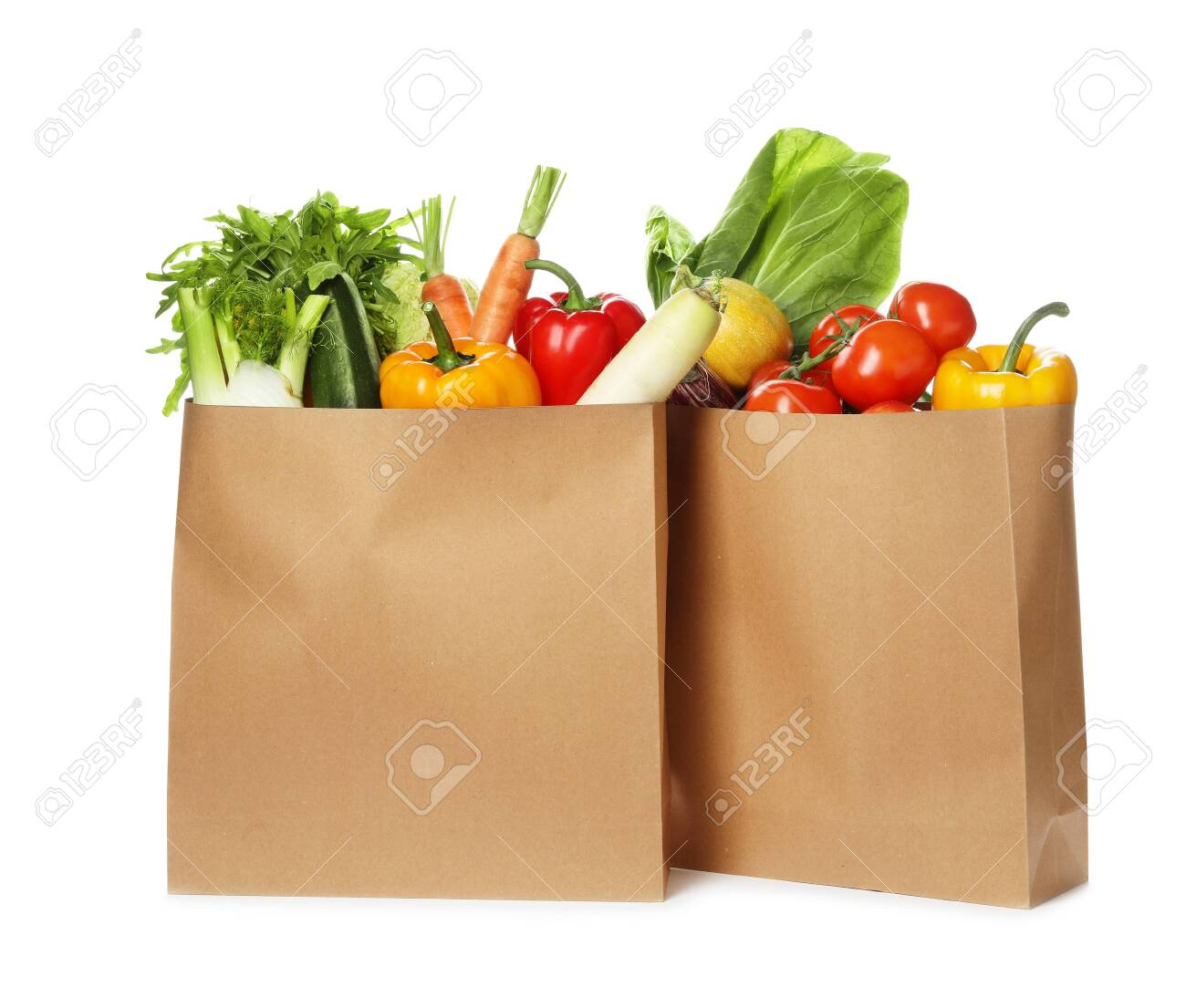 Paper bags with fresh vegetables on white background - 123316641