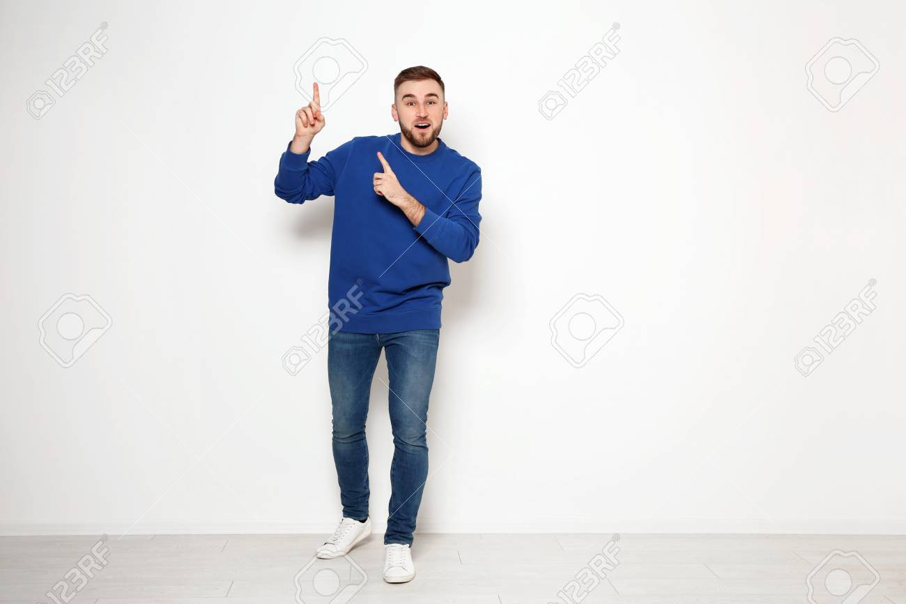Full length portrait of emotional man against white wall. Space for text - 123700928