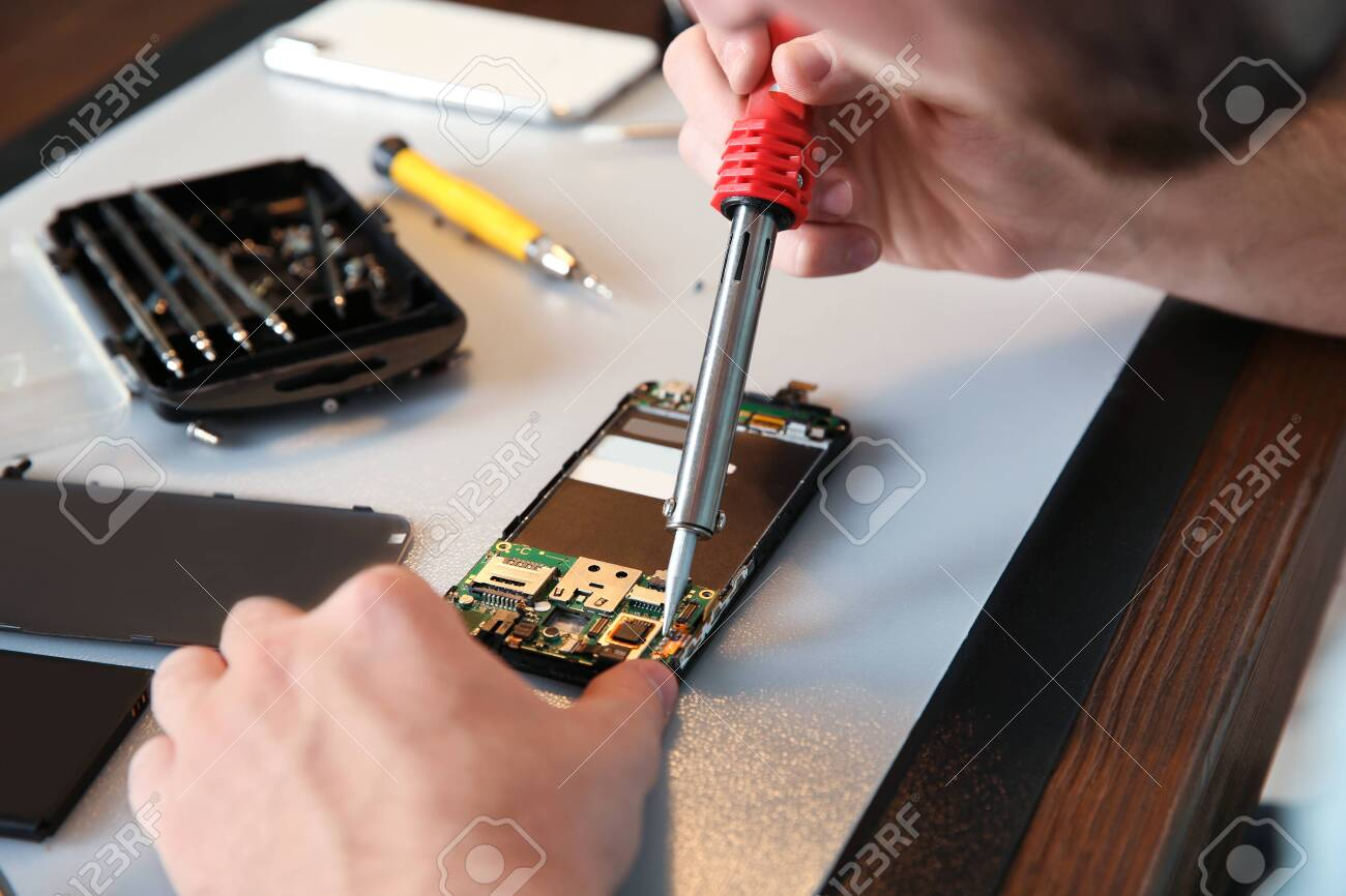 Technician Repairing Mobile Phone At Table Closeup Stock Photo Picture And Royalty Free Image Image 123630174