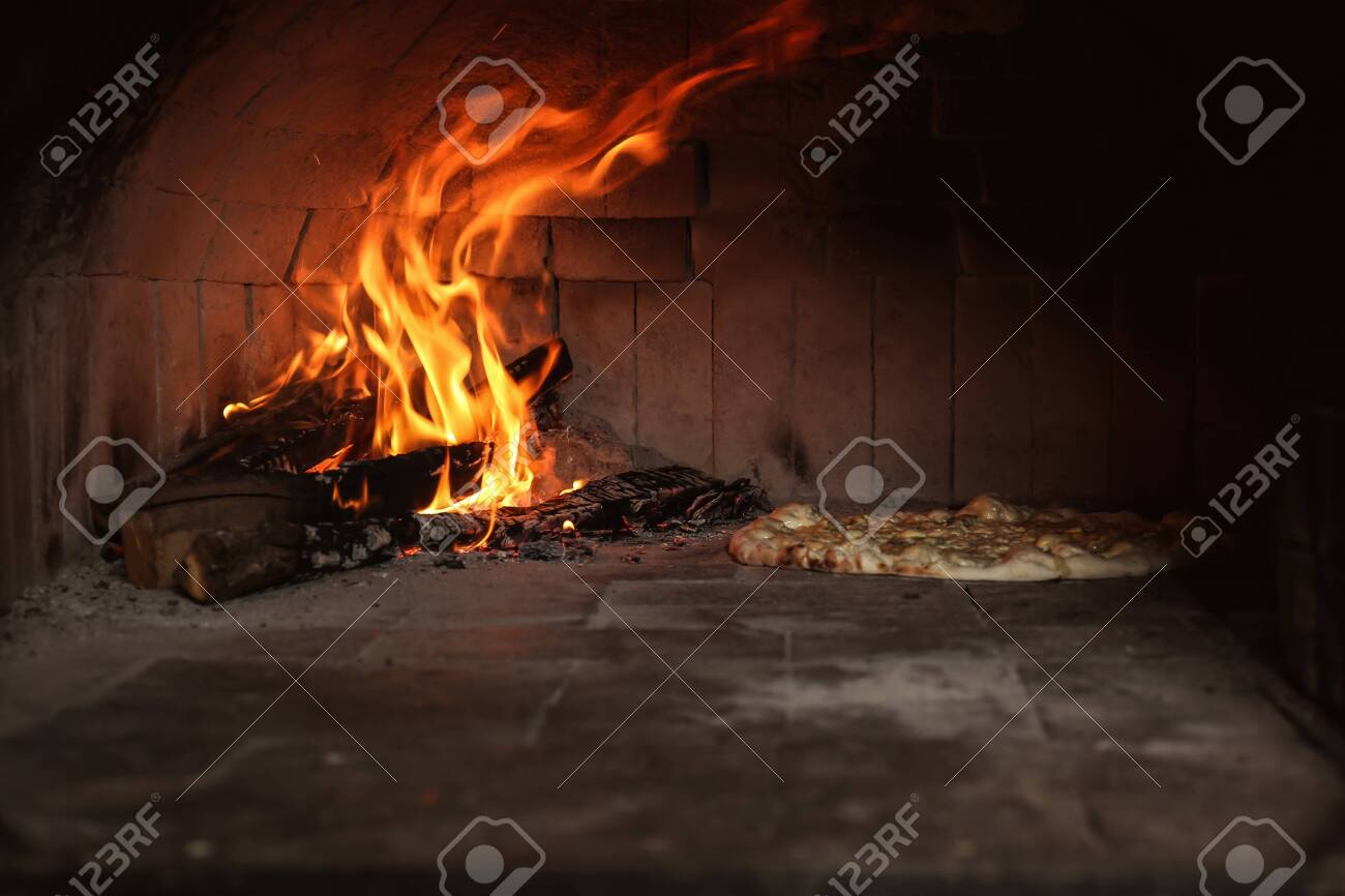 Burning firewood and tasty pizza in oven at restaurant kitchen - 124120143