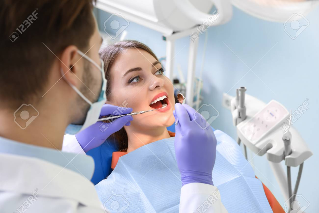 Professional dentist working with patient in modern clinic - 125977547