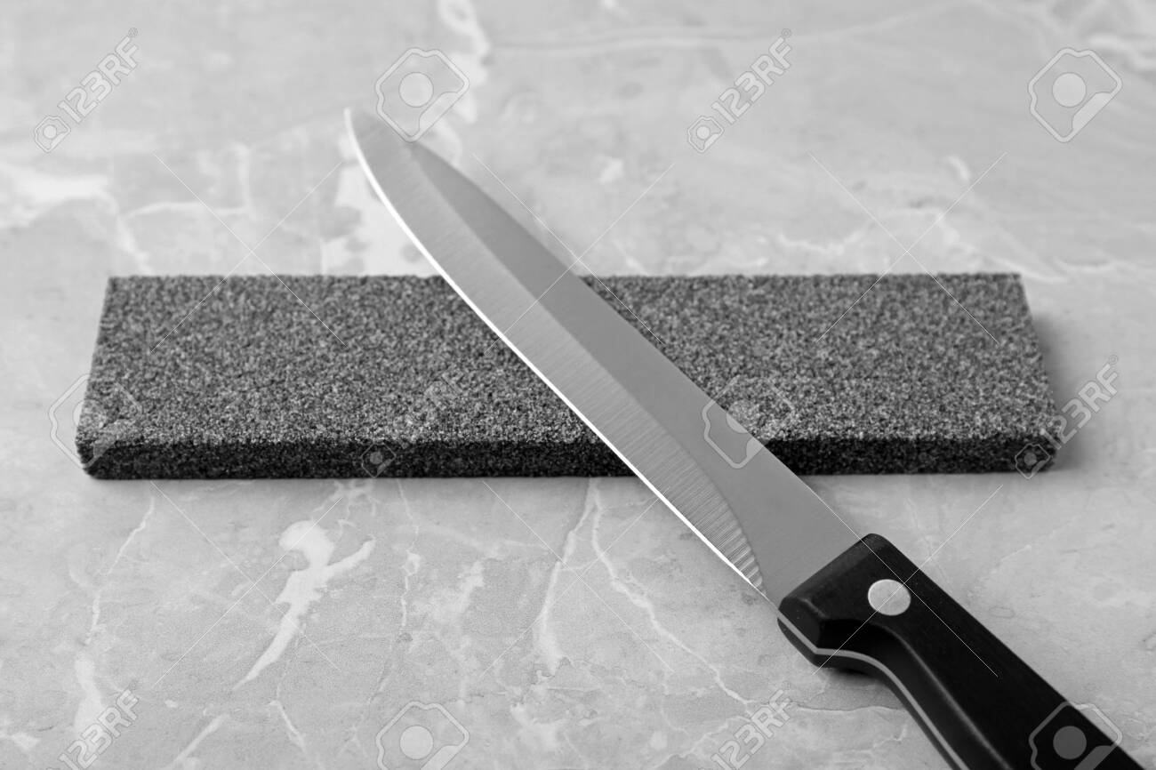 Knife And Sharpening Stone On Grey Background Stock Photo Picture