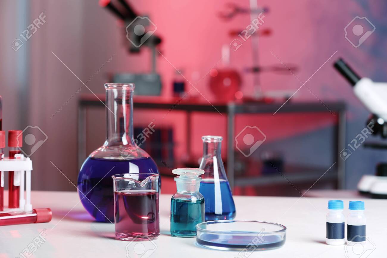 Different glassware with samples on table in chemistry laboratory - 124666470