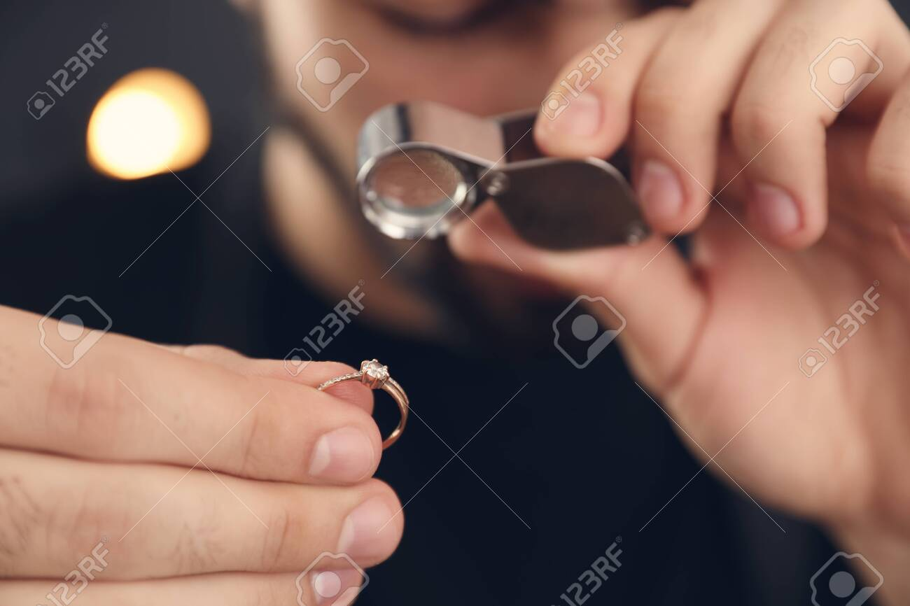 Male jeweler evaluating ring in workshop, closeup - 124804351