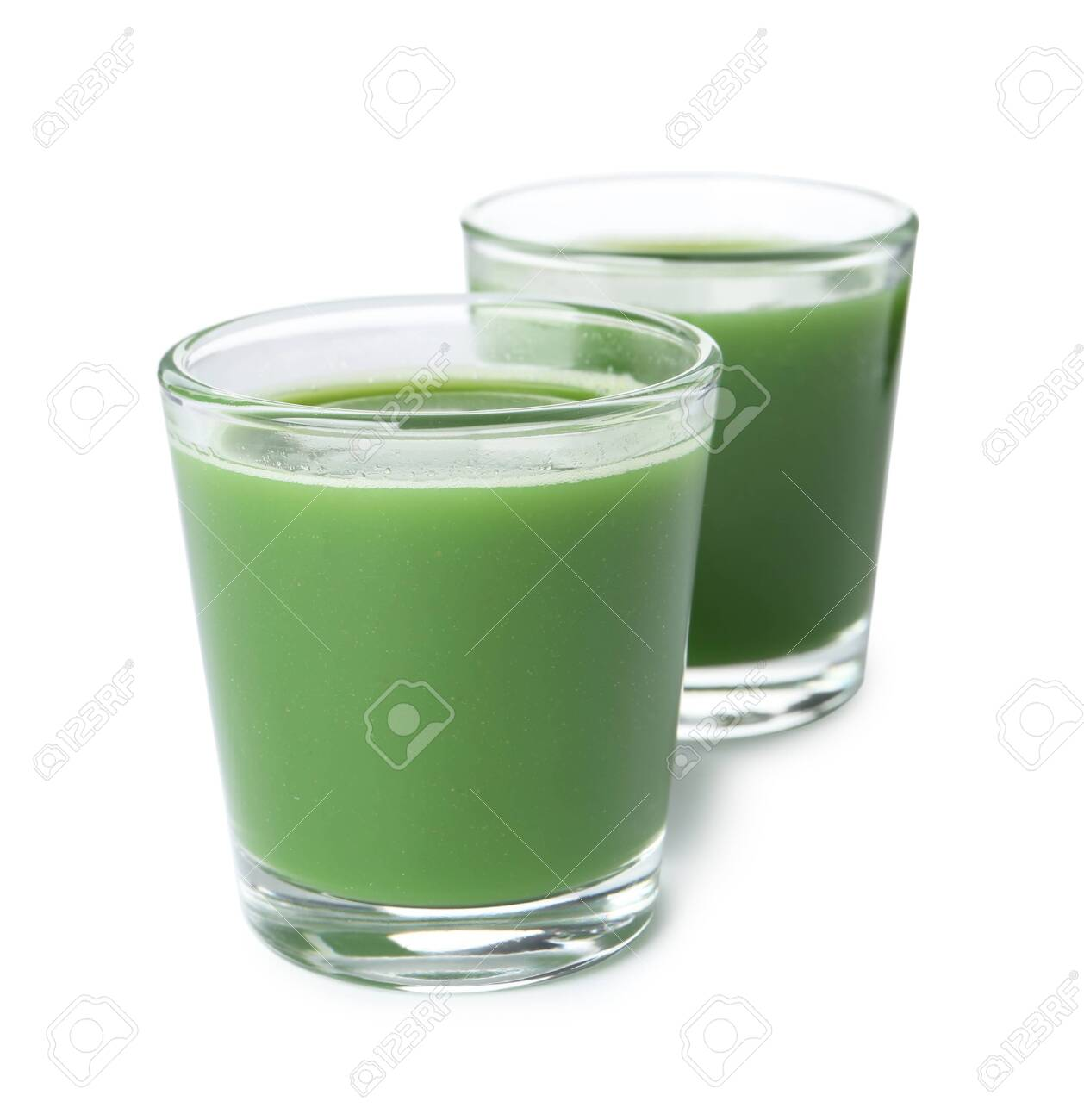 Fresh wheat grass juice in glasses on white background - 124879304