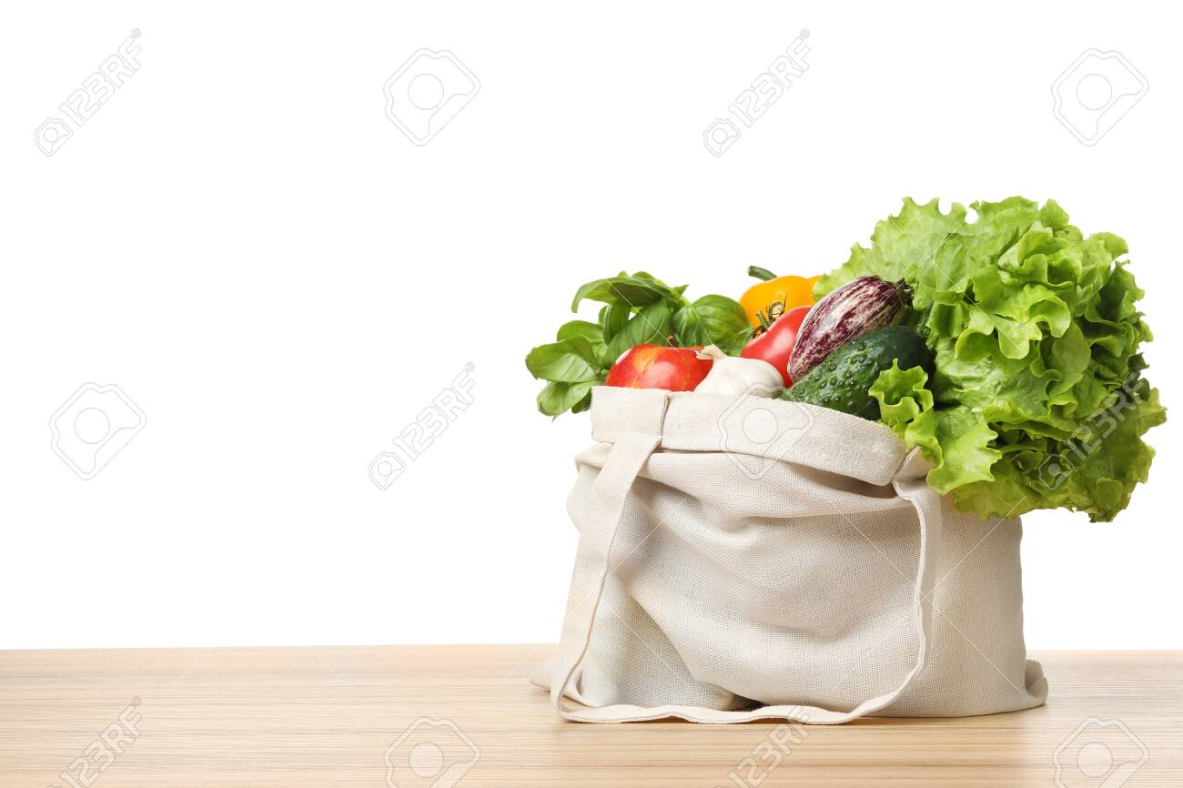 Cloth bag with vegetables on table against white background. Space for text - 124958135