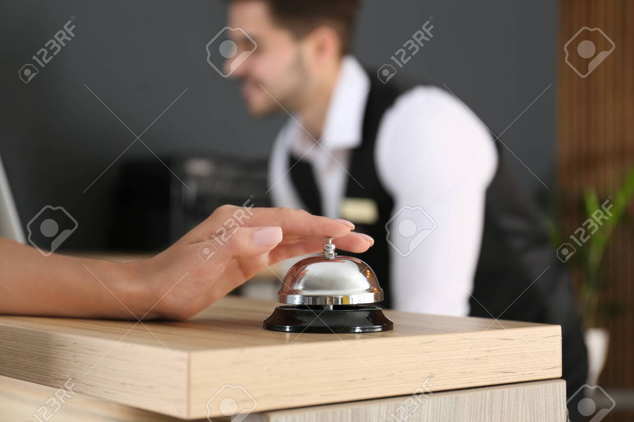 Woman ringing in bell on reception desk, closeup - 126583130