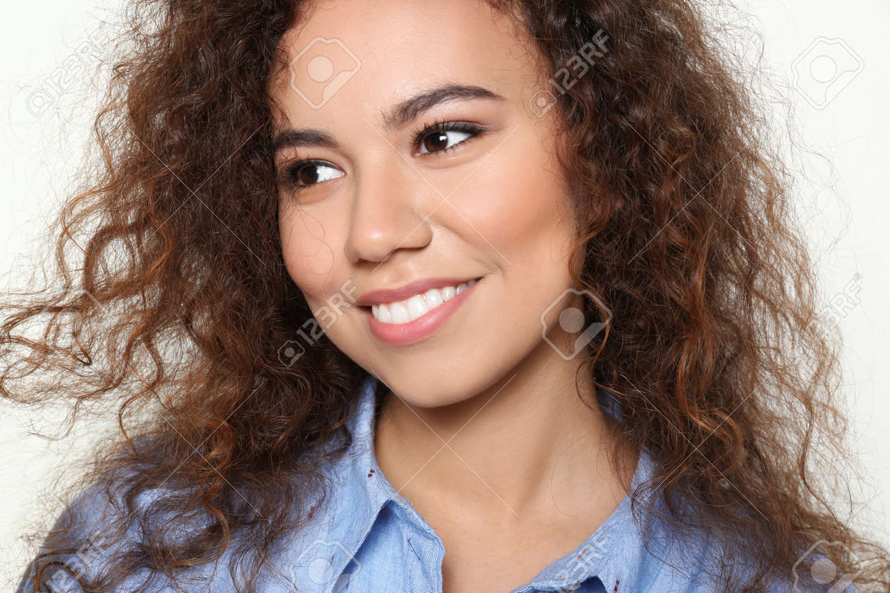 Young African-American woman with beautiful face on light background, closeup - 126024898