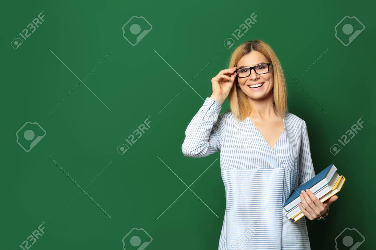 Portrait of beautiful teacher with books near chalkboard, space for text - 126729898