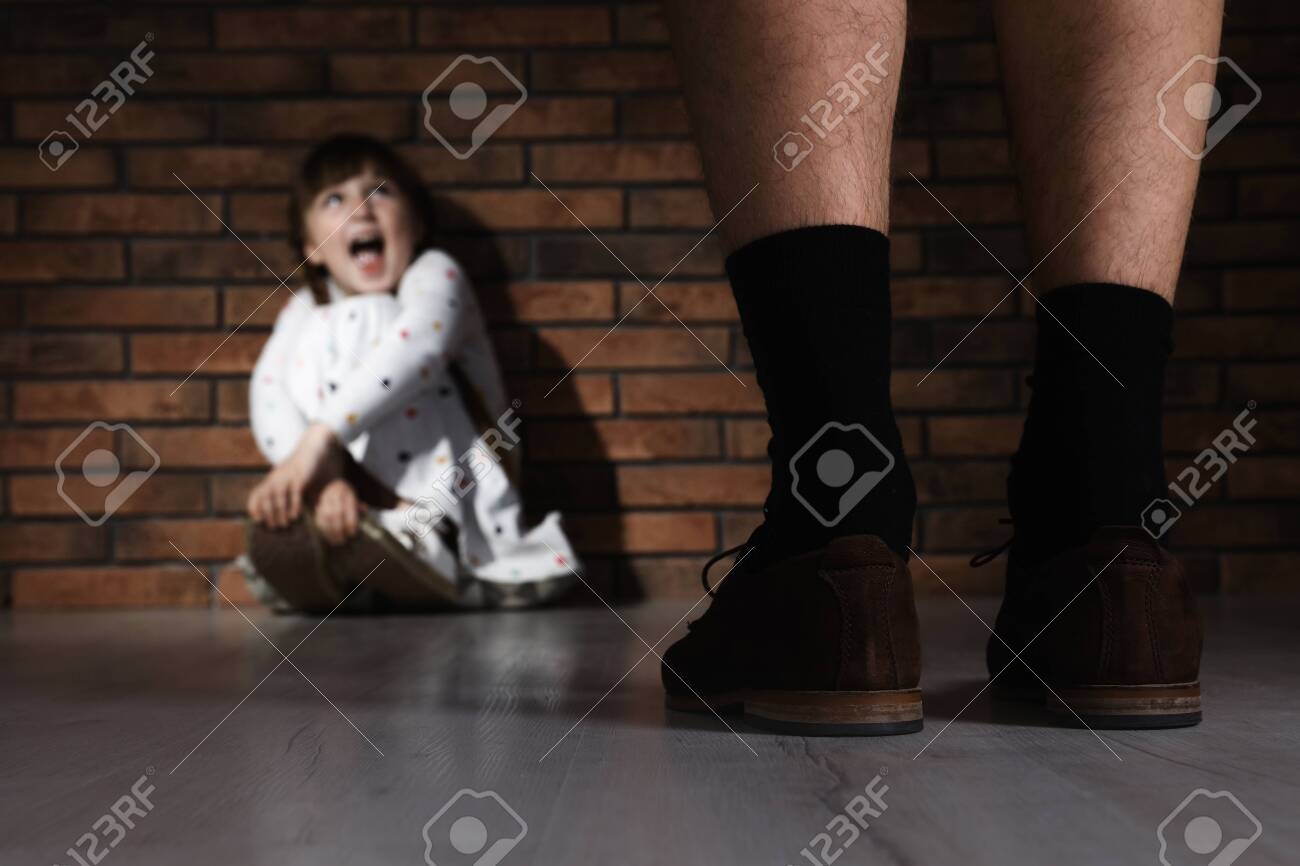 Adult man without pants standing in front of scared little girl indoors. Child in danger - 126788184