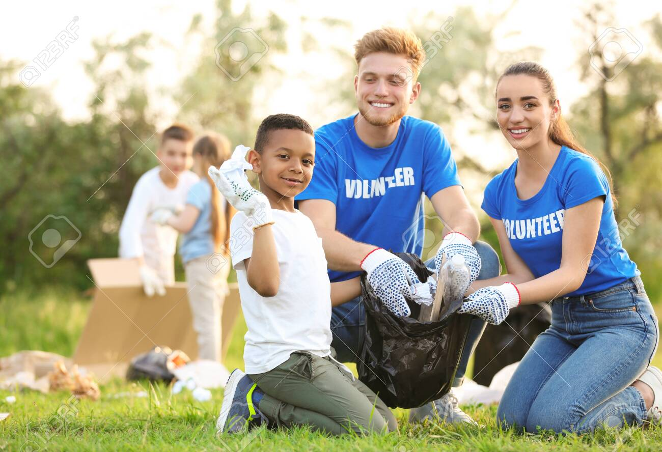Little African-American boy collecting trash with volunteers in park - 126785005