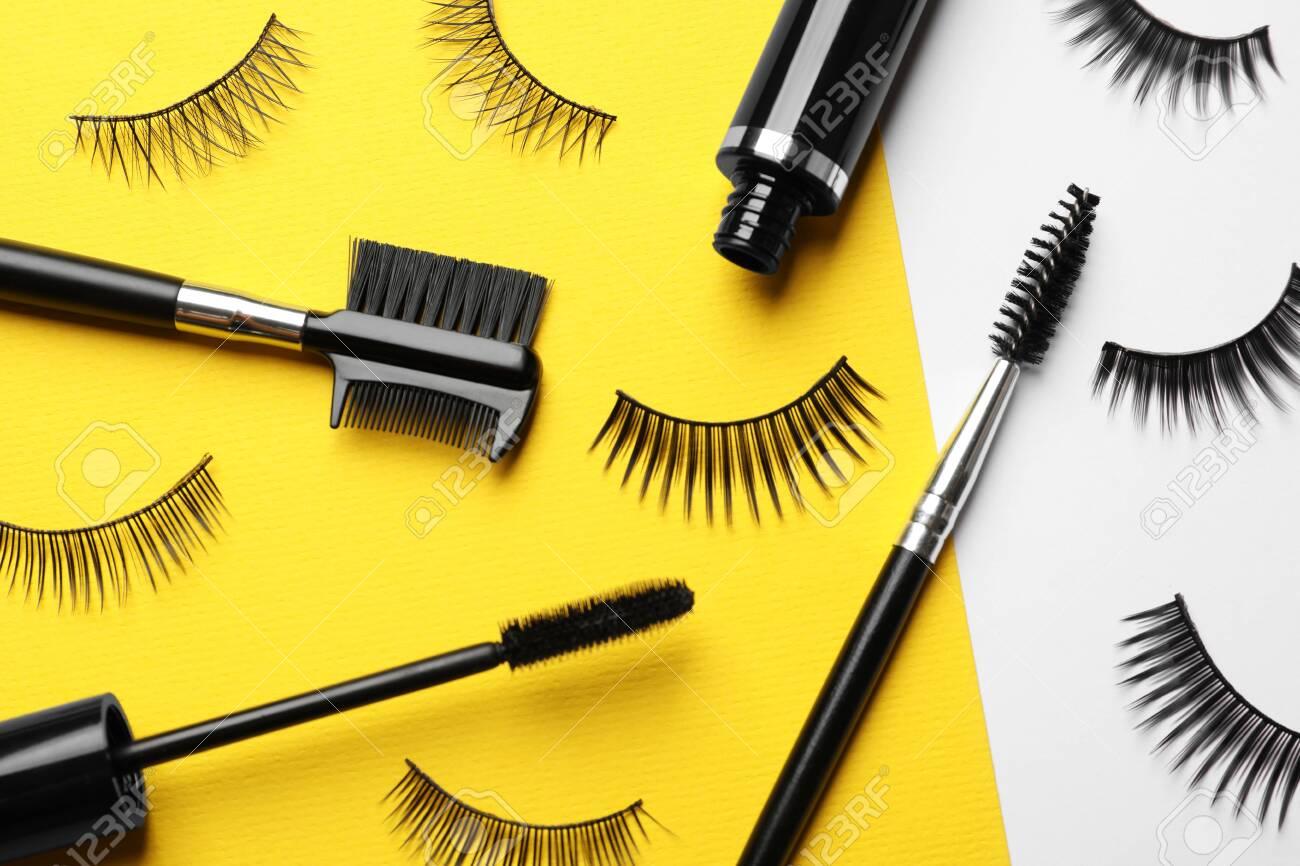 False eyelashes, mascara and brushes on color background, flat lay - 127388750
