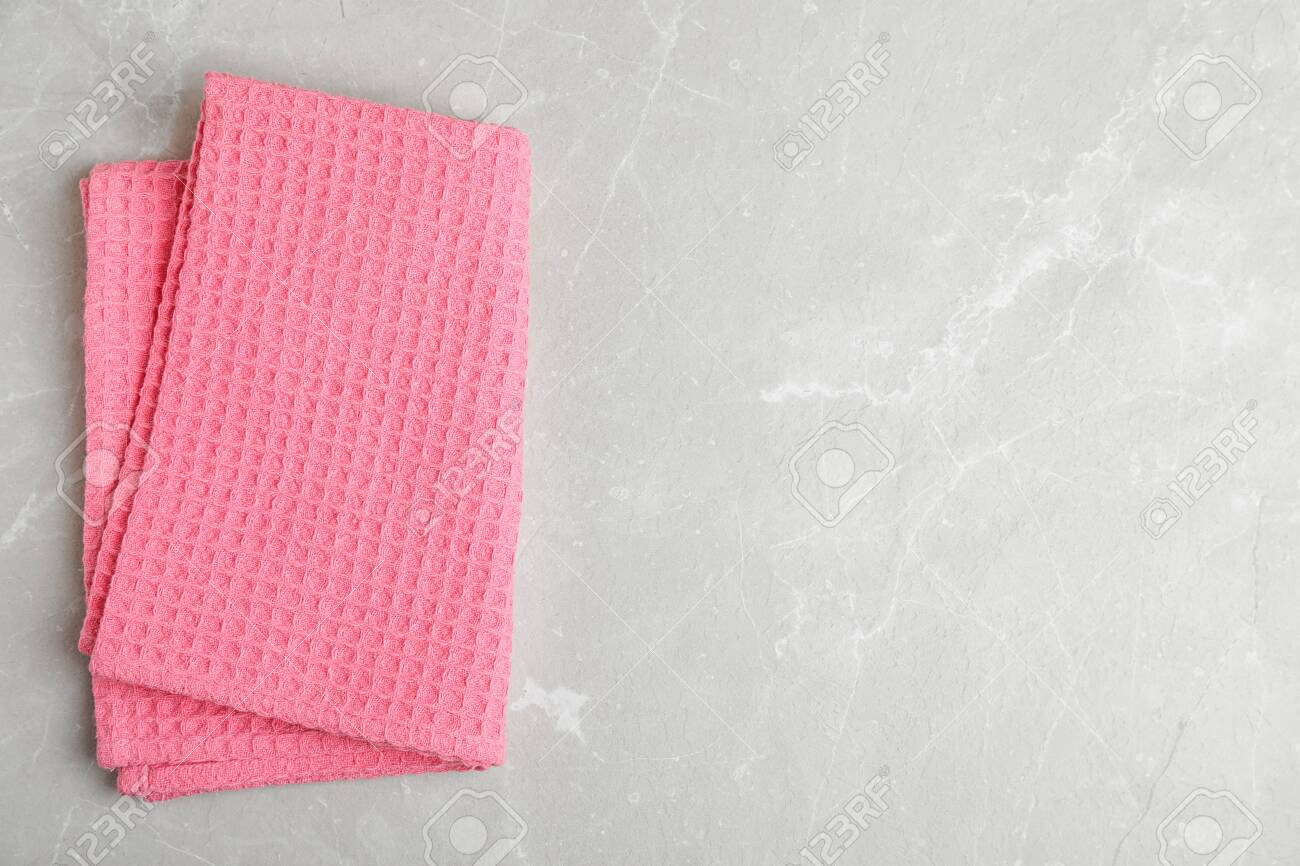 Pink kitchen towel on light marble background, top view. Space..